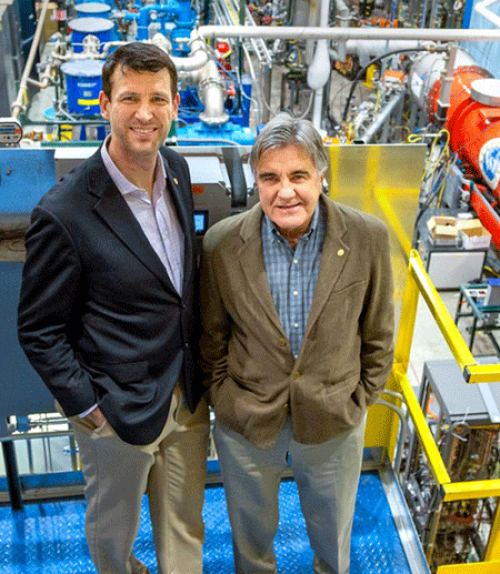 Two physicsists stand in front of accelerator equipment