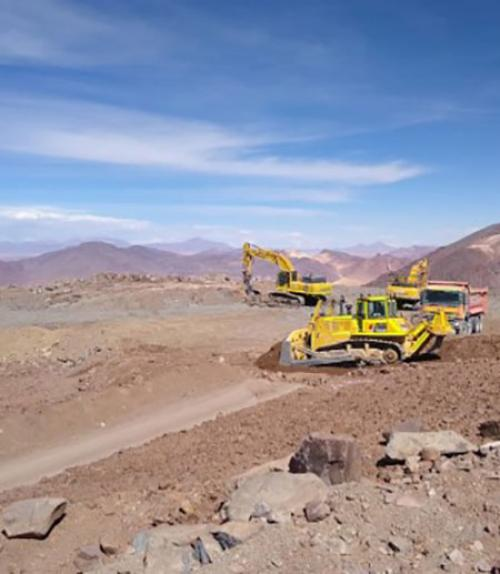 Bulldozers at the site of the telescope, with mountains in the background