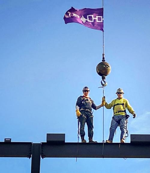 Two ironworkers on top of a beam