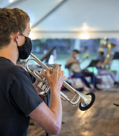 Student playing the trumpet with his fellow classmates in the background