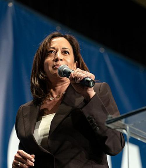 Kamala Harris, holding a microphone on stage
