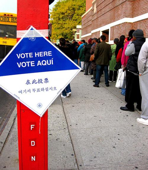 """""""Vote here"""" sign beside a line of people"""