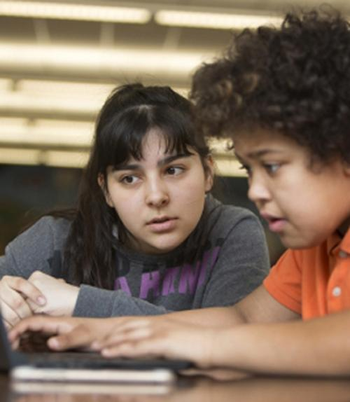 Student working with middle school student