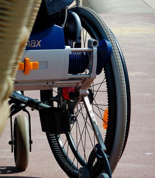 A closeup of the back wheel of a wheelchair