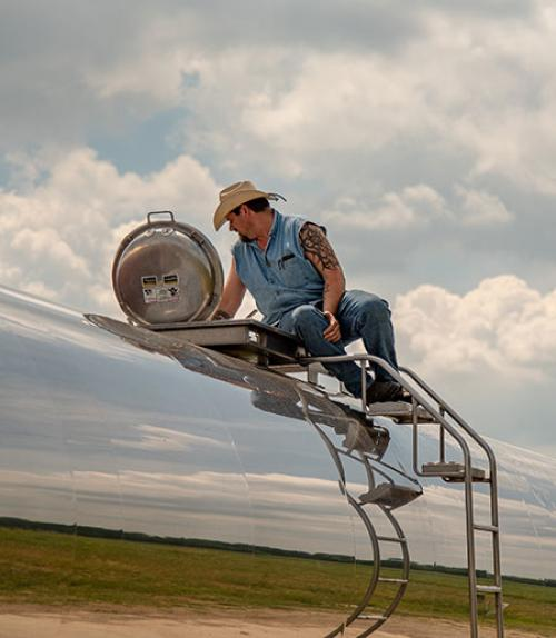 Man with a tattoo on top of a tanker truck with the image of the sky reflected off the metal