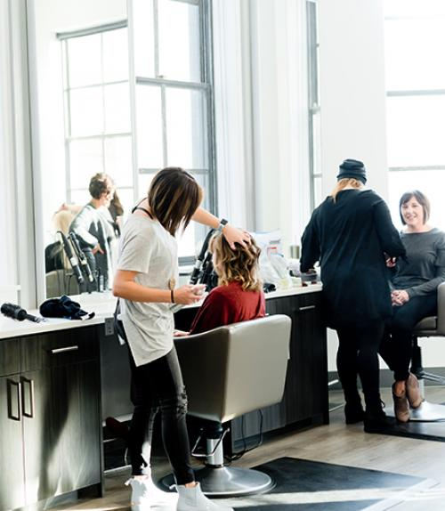Hairdresser working on a client in a bright room