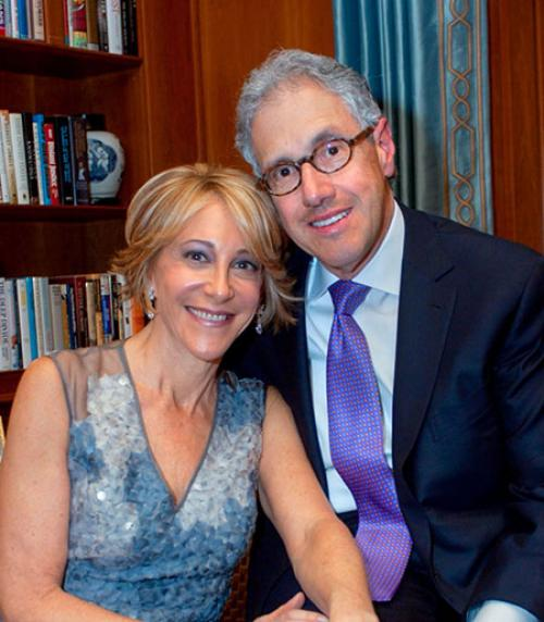 Jan Rock Zubrow '77 and Barry Zubrow. Woman in blue dress leans on man in suit and tie.