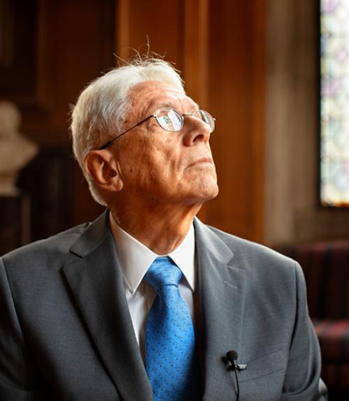 Older man in suit looking towards the ceiling.