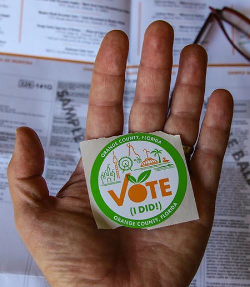 """Hand holding a """"Vote"""" sticker"""