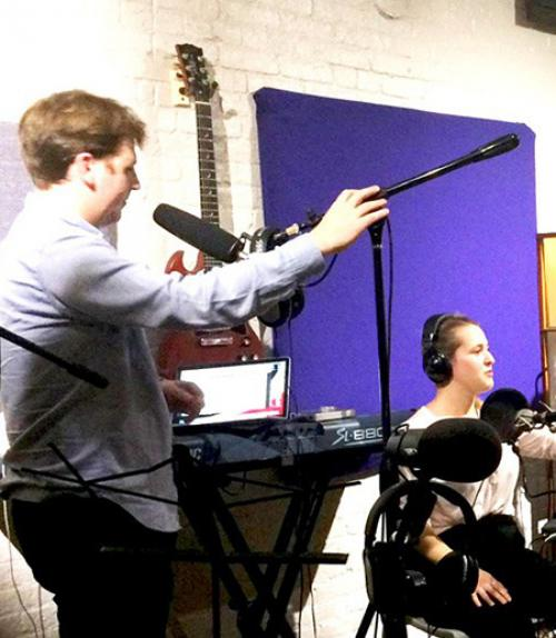 Two people surrounded by recording equipment