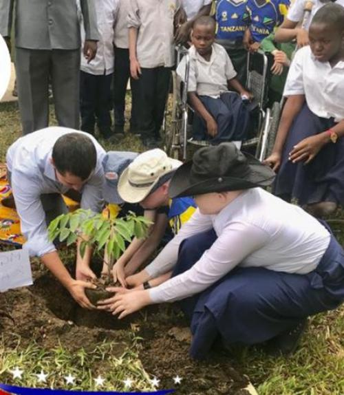 Thomas Nolan plants a tree with students