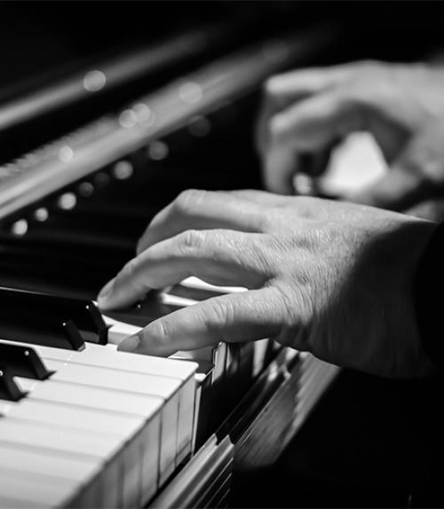 A black and white photo of two hands playing a piano