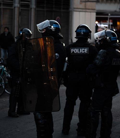 Four police in black, with shields and helmets