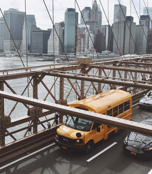 Yellow bus on a bridge, city in the background