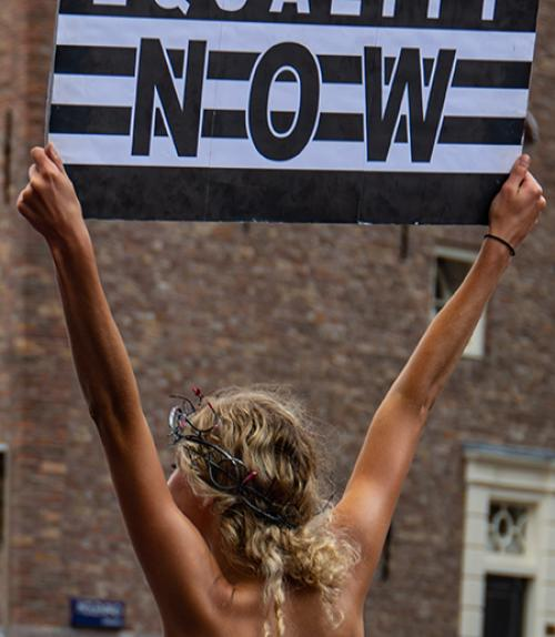 Person holding sign, seen from the back
