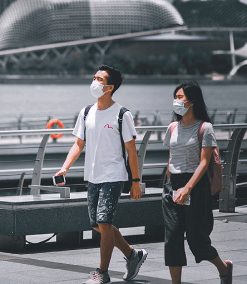 Two people walking, wearing masks