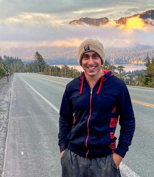 Person standing by a road with mountains in the background
