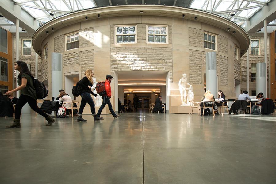 Students walking through the Klarman Hall atrium