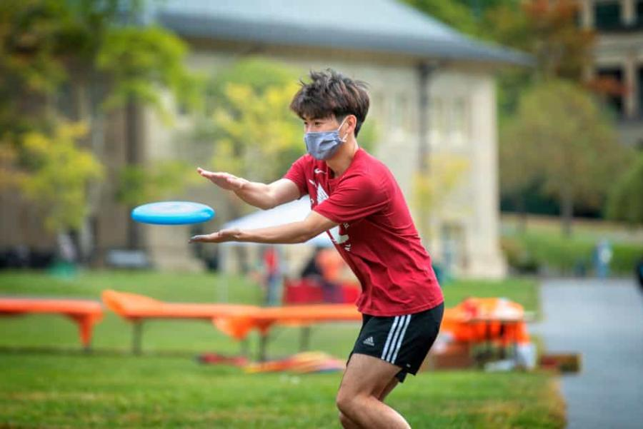 Masked student catches a frisbee
