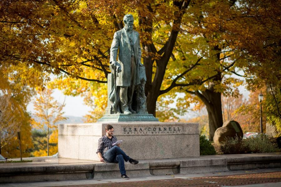 Student reading a book by statue of Ezra Cornell