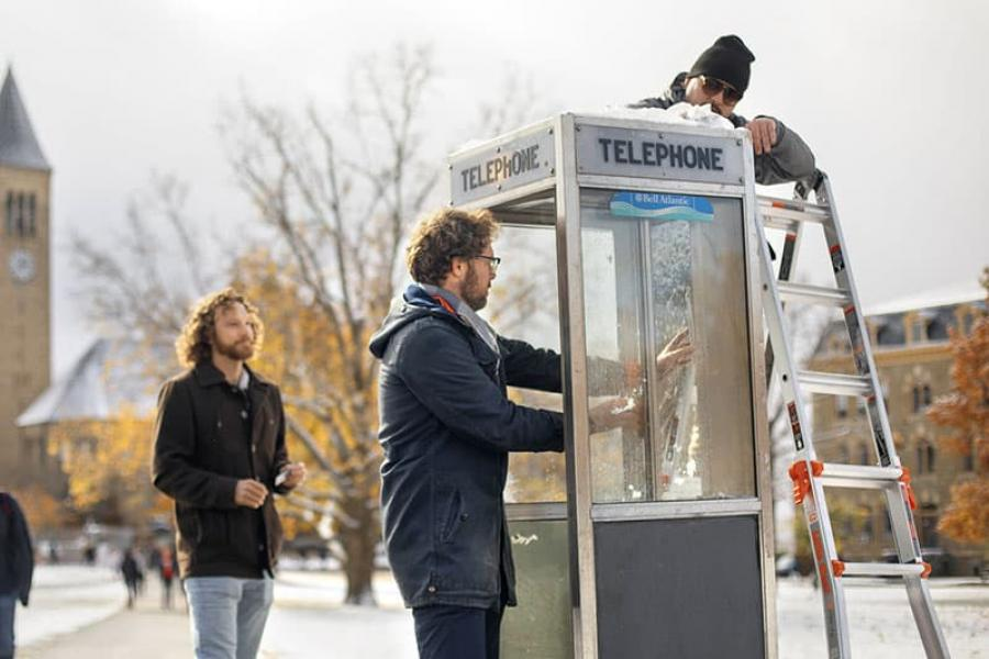 """Sam Harnett, left and Hoff, right, install sound equipment in a phone booth on the Arts Quad, one of five """"listening stations"""" installed around campus as part of the event"""