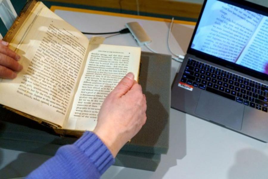 Hands holding a book near a computer screen