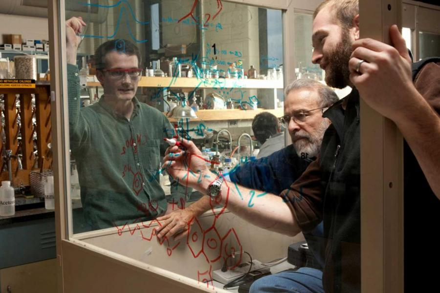 professor and two student write formulas on clear glass