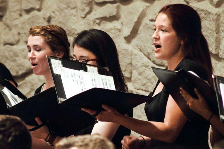 Three people sing in a choir