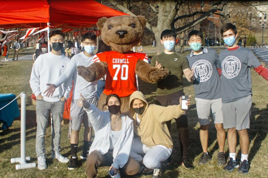 Seven students and the bear mascot, looking happy