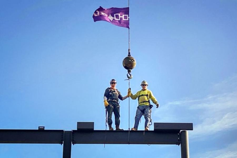 Two people in work hats, atop a building under construction