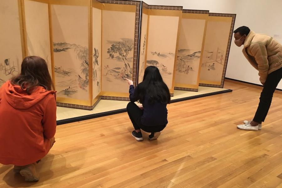Students viewing art on a Japanese screen