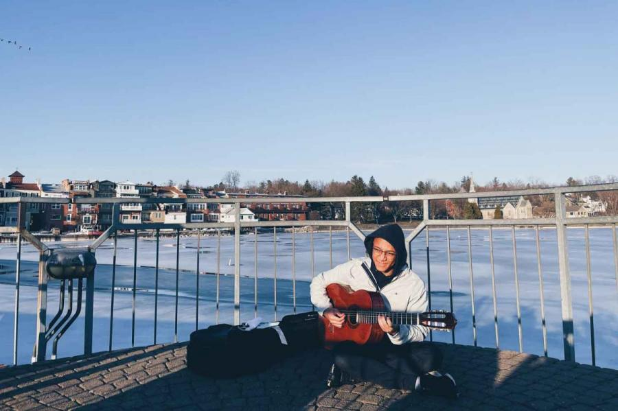 Man playing guitar on a dock