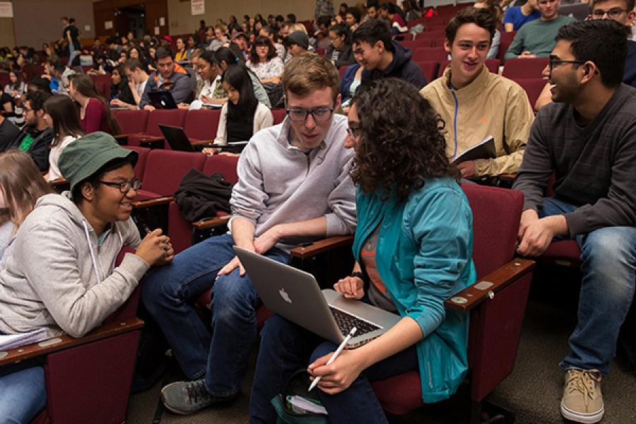 Three students confer over a laptop