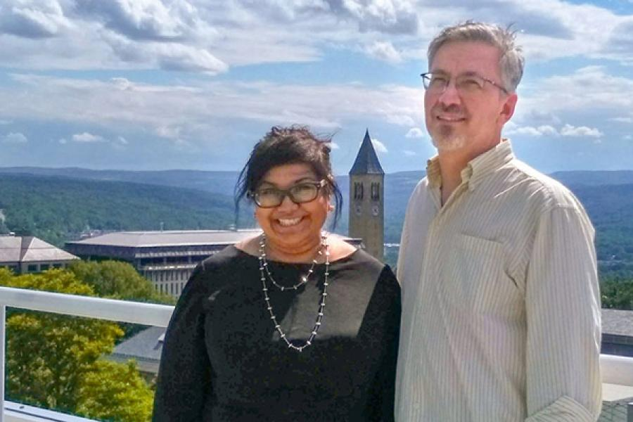 Two people, with Cornell campus in background