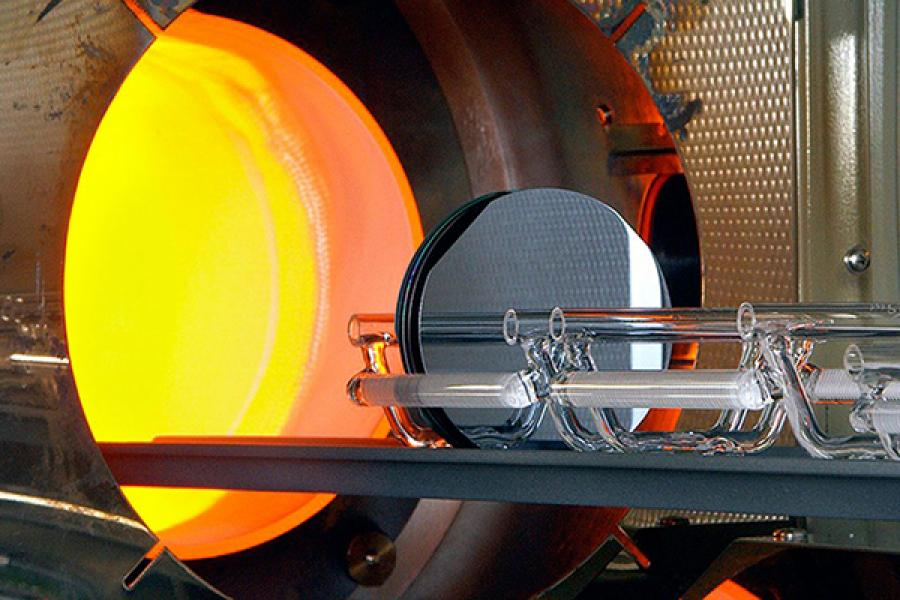 Glass on a tray, entering a glowing orange furnace