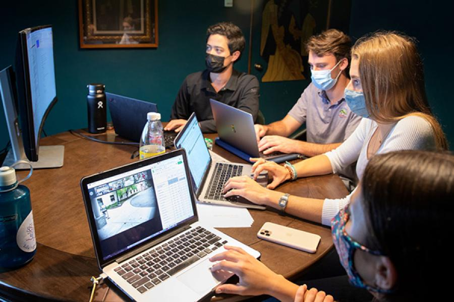 Four students work on lap tops, wearing face masks