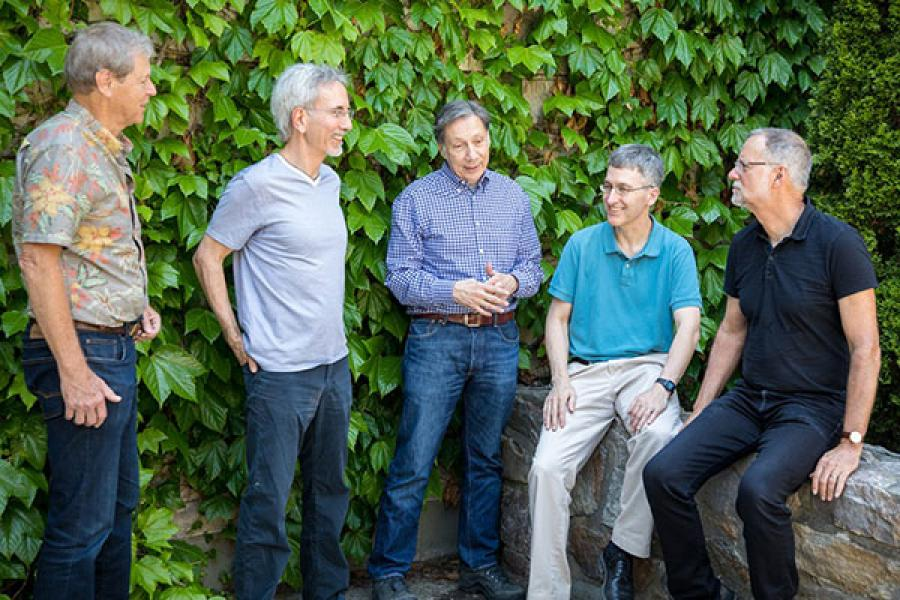 From left: Professors William Schulze, Thomas Gilovich, J. Edward Russo, Ted O'Donoghue and Robert Frank, standing in front of some leafy ivy