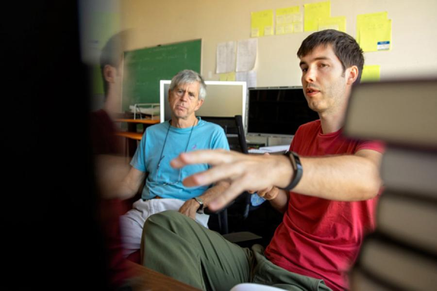 Thomas Davidson, right, a doctoral student in the field of sociology, at work in the Social Dynamics Laboratory run by Michael Macy, back, the Goldwin Smith Professor of Arts and Sciences in sociology.