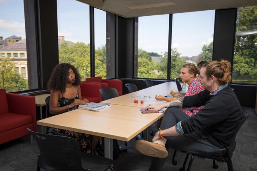 graduate students Kaye Nantah and Chance A. Smith met in the grad lounge to continue a discussion from their morning seminar, while Camille Portier nibbled on her lunch.