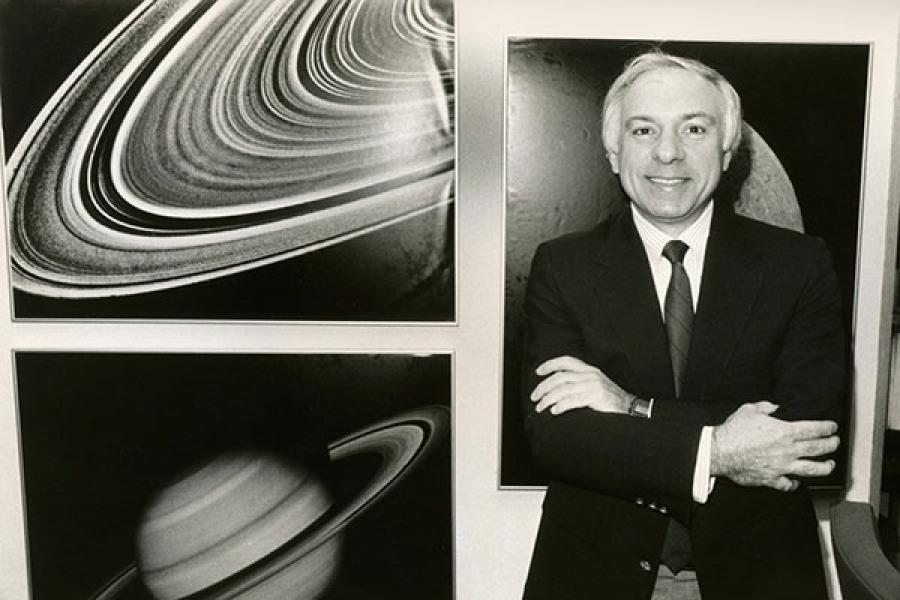 Yervant Terzian standing next to images of Saturn and of Saturn's rings