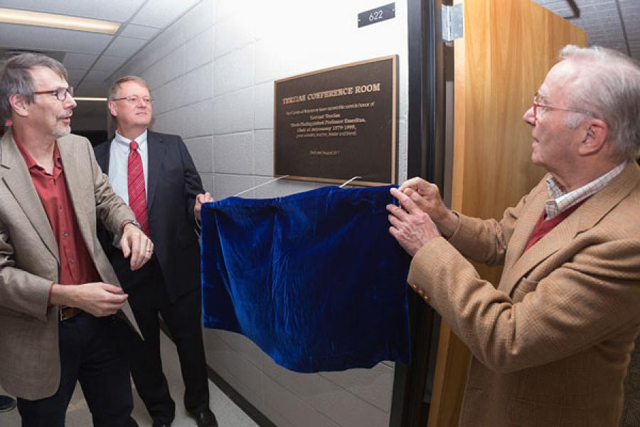 Astronomy chair Terry Herter, Chuck Mund and Robert Cowie uncovering plaque
