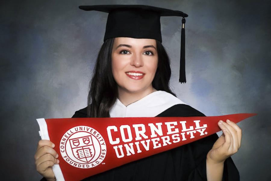 Edy Kennedy in cap and gown with Cornell banner