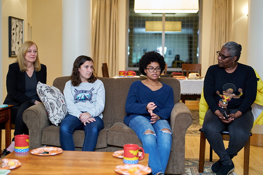 Students sitting on couch listening to a conversation.