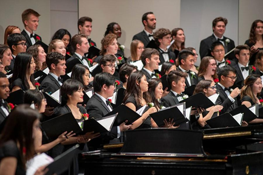 People singing in formal clothes on stage