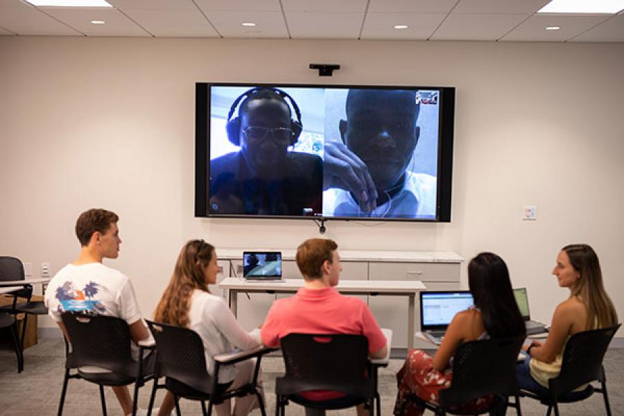 Human to Human team members in a classroom facing a large videoscreen talking to Beta project partners