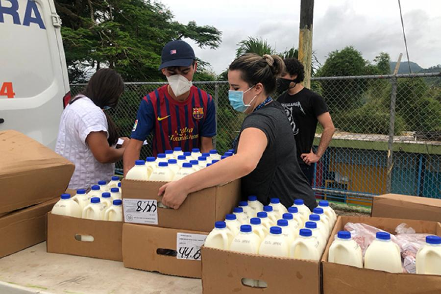 Joey Ibanez, left, unloads milk during a delivery, helped by his cousin, right, Isabell Junqueria.