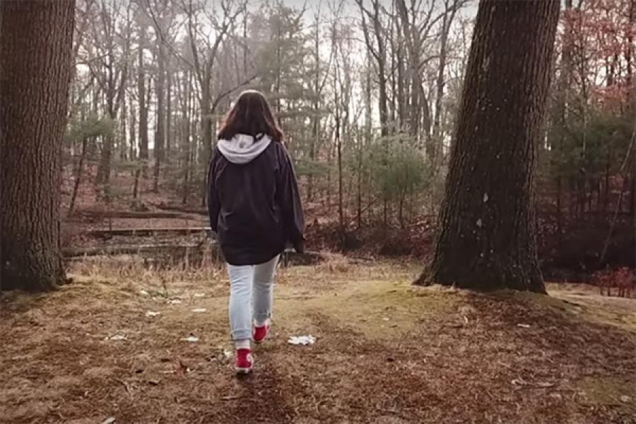 student walking in woods