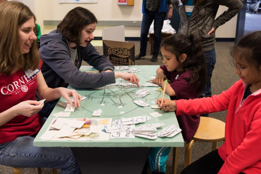 Graduate students Samantha Peck, front left, and Caitlyn Finton work with Thora Iyer and Ada Iyer on the Imagine That! exhibit at the Sciencenter in Ithaca.
