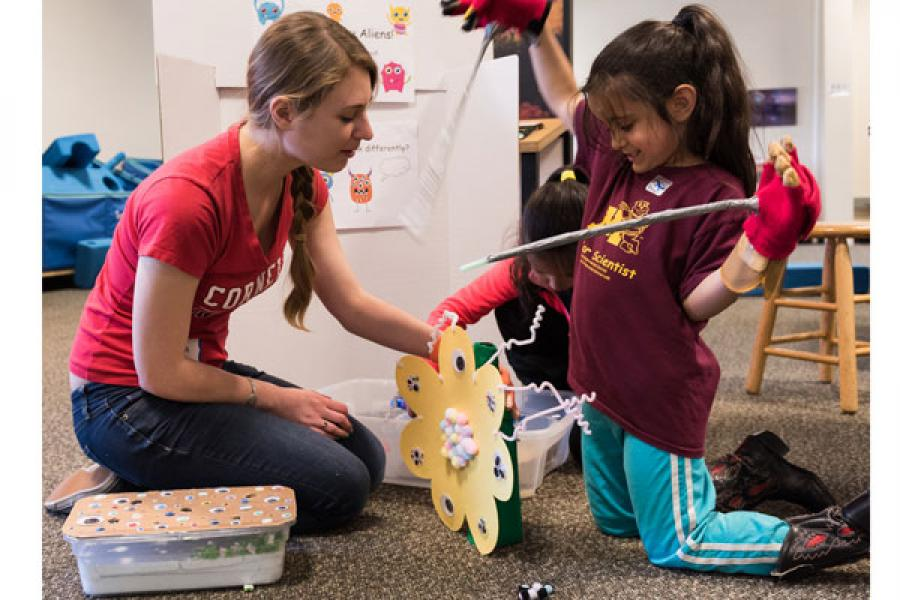 Graduate student Melissa Elston works with Thora Iyer at the Sciencenter, using the Hungry Aliens exhibit gloves