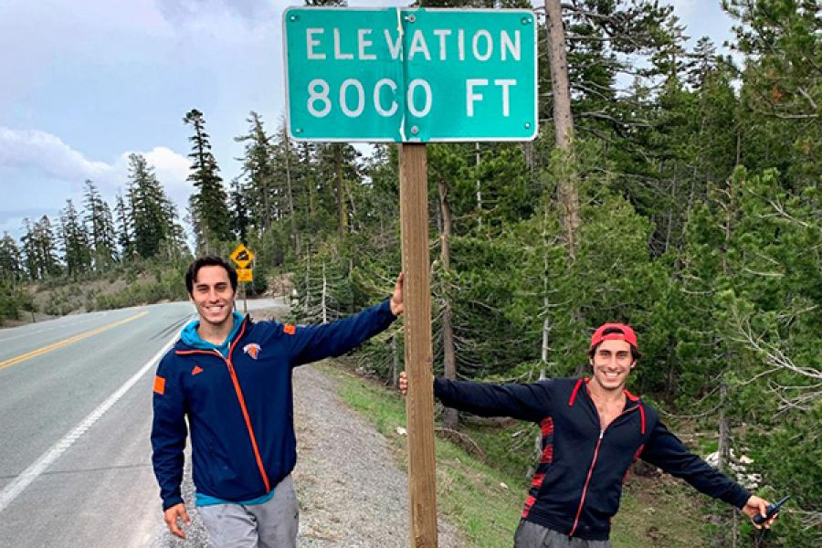 Two people flank a sign: 8,000 feet